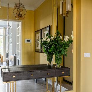 Inredning av en klassisk mellanstor ingång och ytterdörr, med gula väggar, laminatgolv, en enkeldörr, en vit dörr och beiget golv