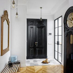На фото: входная дверь в стиле фьюжн с белыми стенами, светлым паркетным полом, черной входной дверью и одностворчатой входной дверью