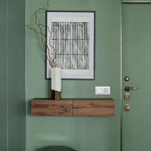 Cette image montre une petit entrée design avec un couloir, un mur vert, un sol en carrelage de porcelaine, une porte simple, une porte verte et un sol gris.