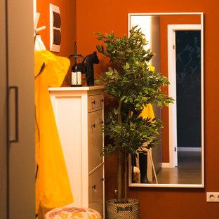 Inspiration pour une petit porte d'entrée nordique avec un mur orange, sol en stratifié, une porte simple, une porte blanche et un sol marron.