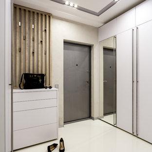 Imagen de puerta principal actual con paredes beige, puerta simple, puerta gris, suelo blanco y suelo de cemento