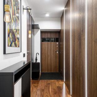 Свежая идея для дизайна: входная дверь в современном стиле с белыми стенами, паркетным полом среднего тона, одностворчатой входной дверью, входной дверью из дерева среднего тона и коричневым полом - отличное фото интерьера
