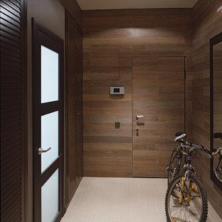 На фото: входная дверь в современном стиле с коричневыми стенами, одностворчатой входной дверью, входной дверью из дерева среднего тона и бежевым полом