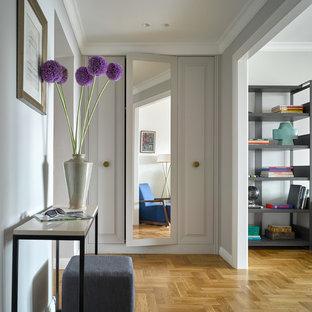 Новые идеи обустройства дома: прихожая в стиле современная классика с белыми стенами и паркетным полом среднего тона