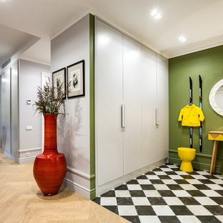 Ispirazione per un ingresso con vestibolo contemporaneo di medie dimensioni con pareti verdi, pavimento con piastrelle in ceramica, una porta singola, una porta bianca e pavimento bianco