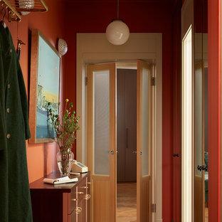 Cette image montre une entrée minimaliste avec un mur orange, un sol gris et un couloir.