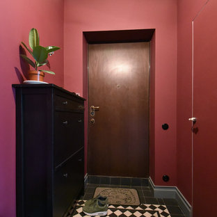 This is an example of a small contemporary front door in Moscow with red walls, ceramic flooring, a single front door, a dark wood front door and black floors.