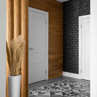 Идея дизайна: входная дверь среднего размера в современном стиле с черными стенами, полом из керамогранита, одностворчатой входной дверью, белой входной дверью, серым полом и кирпичными стенами