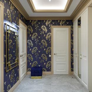Пример оригинального дизайна: входная дверь среднего размера в стиле неоклассика (современная классика) с синими стенами, серым полом и правильным освещением