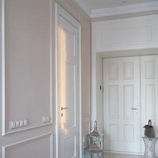 На фото: входная дверь в стиле неоклассика (современная классика) с бежевыми стенами, двустворчатой входной дверью, белой входной дверью и бежевым полом с