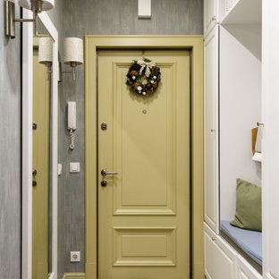 Foto på en liten vintage hall, med grå väggar, en enkeldörr, en gul dörr och flerfärgat golv