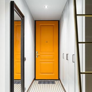 Bild på en liten funkis ingång och ytterdörr, med grå väggar, klinkergolv i keramik, en enkeldörr och en gul dörr