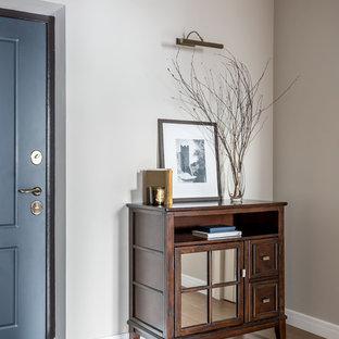 Свежая идея для дизайна: узкая прихожая в стиле современная классика с серыми стенами, паркетным полом среднего тона, одностворчатой входной дверью, синей входной дверью и бежевым полом - отличное фото интерьера
