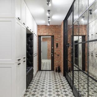 На фото: входная дверь среднего размера в стиле лофт с оранжевыми стенами, полом из керамогранита, одностворчатой входной дверью, черной входной дверью и белым полом