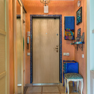 Entryway - small mediterranean ceramic floor entryway idea in Saint Petersburg with a light wood front door and orange walls
