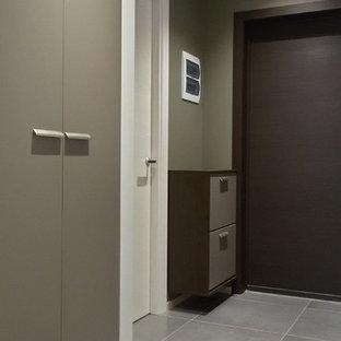 サンクトペテルブルクの小さい片開きドアコンテンポラリースタイルのおしゃれな玄関ドア (緑の壁、磁器タイルの床、濃色木目調のドア、グレーの床) の写真