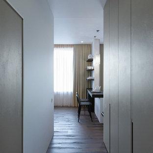 Immagine di un piccolo corridoio minimal con pavimento in laminato, pavimento marrone e pareti beige