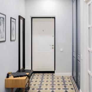 На фото: узкая прихожая в стиле современная классика с белыми стенами, одностворчатой входной дверью, белой входной дверью, бетонным полом и разноцветным полом с