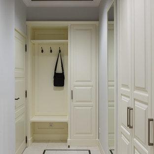 Идея дизайна: большая узкая прихожая в стиле современная классика с серыми стенами, полом из керамической плитки, одностворчатой входной дверью, белой входной дверью и бежевым полом
