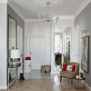 Идея дизайна: входная дверь в стиле неоклассика (современная классика) с одностворчатой входной дверью, белой входной дверью, белым полом, серыми стенами и правильным освещением