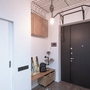 Example of a mid-sized urban laminate floor and brown floor entryway design in Moscow with white walls and a black front door