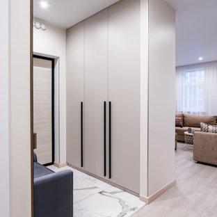 Стильный дизайн: входная дверь в современном стиле с одностворчатой входной дверью, входной дверью из светлого дерева и белым полом - последний тренд