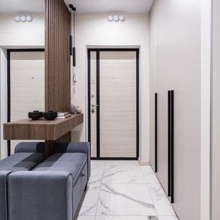 Modern inredning av en ingång och ytterdörr, med vita väggar, en enkeldörr, ljus trädörr och vitt golv