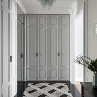 На фото: узкая прихожая среднего размера в стиле неоклассика (современная классика) с серыми стенами, мраморным полом, одностворчатой входной дверью, серой входной дверью и разноцветным полом
