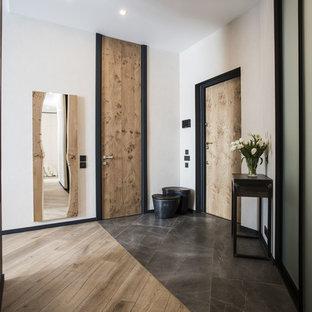 Стильный дизайн: прихожая в современном стиле с белыми стенами, одностворчатой входной дверью, входной дверью из светлого дерева и коричневым полом - последний тренд