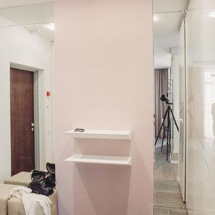 モスクワの片開きドアコンテンポラリースタイルのおしゃれな玄関 (ピンクの壁、濃色木目調のドア) の写真