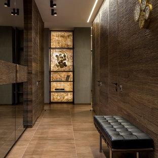Пример оригинального дизайна: узкая прихожая среднего размера в современном стиле с коричневыми стенами, полом из керамогранита и коричневым полом