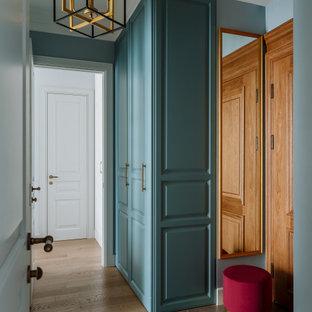 Idéer för att renovera en liten vintage ingång och ytterdörr, med blå väggar, mellanmörkt trägolv, en enkeldörr, mellanmörk trädörr och brunt golv