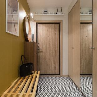 Aménagement d'une porte d'entrée contemporaine avec un mur jaune, une porte simple, une porte en bois brun et un sol multicolore.