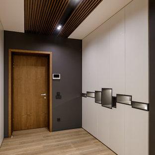 На фото: входная дверь среднего размера в современном стиле с серыми стенами, паркетным полом среднего тона, одностворчатой входной дверью, входной дверью из дерева среднего тона и бежевым полом с