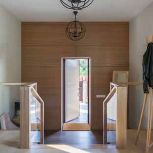Удачное сочетание для дизайна помещения: входная дверь в современном стиле с белыми стенами, одностворчатой входной дверью, входной дверью из светлого дерева и коричневым полом - самое интересное для вас