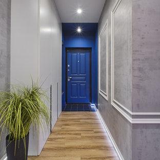 Réalisation d'une petite porte d'entrée urbaine avec un mur gris, sol en stratifié, une porte simple, une porte bleue et un sol beige.