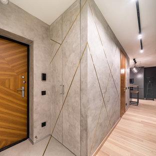 На фото: входная дверь в современном стиле с серыми стенами, одностворчатой входной дверью, входной дверью из дерева среднего тона, светлым паркетным полом и бежевым полом