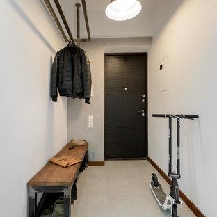 Cette photo montre une porte d'entrée industrielle avec un mur blanc, une porte simple et une porte noire.