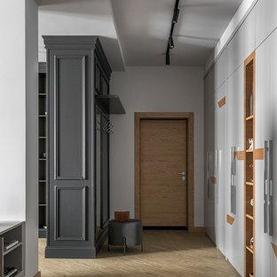 Cette image montre une entrée design de taille moyenne avec un couloir, un mur gris, un sol en vinyl, une porte simple, une porte en bois brun et un sol jaune.