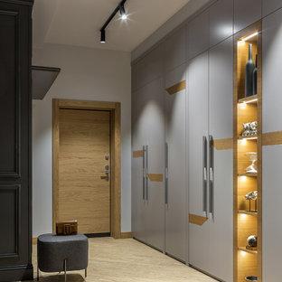Стильный дизайн: входная дверь среднего размера в современном стиле с серыми стенами, полом из винила, одностворчатой входной дверью, входной дверью из дерева среднего тона, бежевым полом и правильным освещением - последний тренд