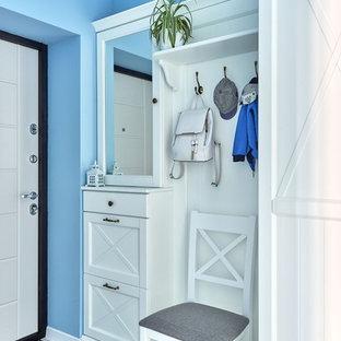 Réalisation d'une entrée marine avec un vestiaire, un mur bleu, une porte simple et une porte blanche.