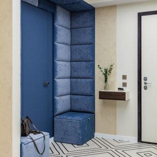 Стильный дизайн: входная дверь в современном стиле с бежевыми стенами, одностворчатой входной дверью, синей входной дверью и панелями на части стены - последний тренд