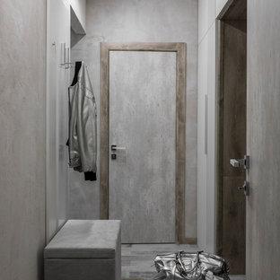 На фото: узкая прихожая в современном стиле с серыми стенами и серым полом с