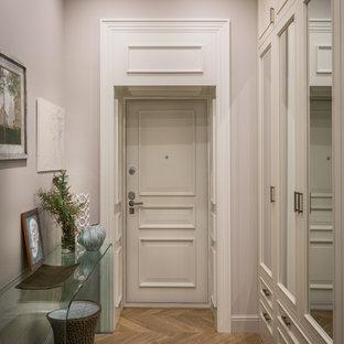 Идея дизайна: узкая прихожая в стиле современная классика с паркетным полом среднего тона, одностворчатой входной дверью, белой входной дверью, коричневым полом и серыми стенами
