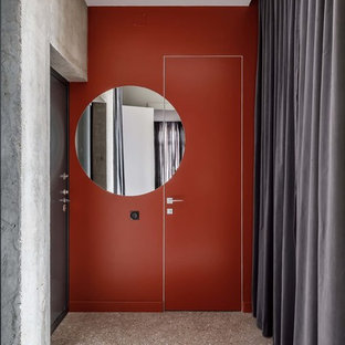 На фото: входная дверь в современном стиле с оранжевыми стенами, полом из терраццо, одностворчатой входной дверью, черной входной дверью и серым полом с