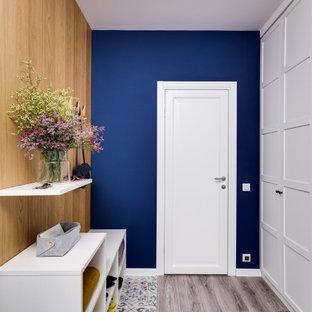 Idées déco pour une entrée contemporaine avec un mur bleu.