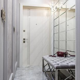 Идея дизайна: узкая прихожая среднего размера в стиле современная классика с серыми стенами, одностворчатой входной дверью, белой входной дверью и серым полом