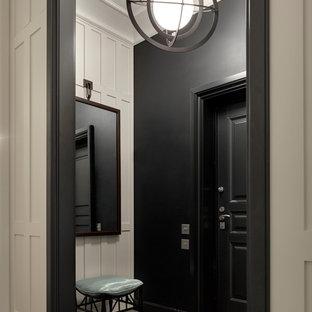 Пример оригинального дизайна интерьера: входная дверь в стиле современная классика с черными стенами, одностворчатой входной дверью, черной входной дверью и серым полом