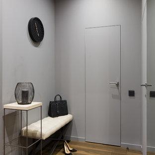 Пример оригинального дизайна: маленький вестибюль в современном стиле с серыми стенами, полом из керамогранита и коричневым полом