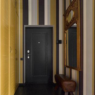 На фото: входные двери в стиле фьюжн с разноцветными стенами, одностворчатой входной дверью и черной входной дверью